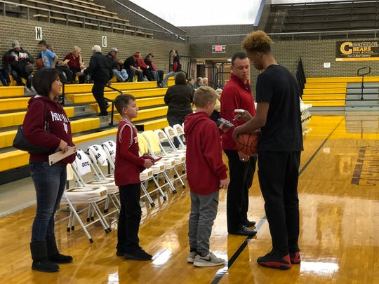 Romeo Langford (right) signs autographs for a pair of young admirers Thursday at Central High School.