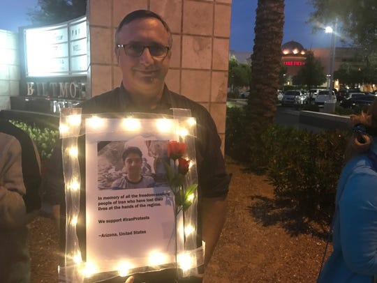 Bob Dalpe carries a sign with a picture of an 11-year-old