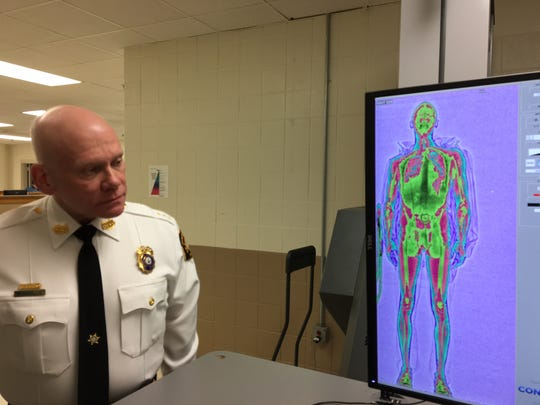 Morris County jail Undersheriff Alan Robinson checks the anatomical image of an inmate projected from a new body imaging scanner at the facility.