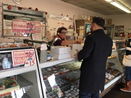 At Sisters Cakery in Detroit's Warrendale sector, Kata Zlatich helps Dearborn attorney Hassan Bazzi with his order of six dozen paczki. Zlatich's father bought the business in 1970.