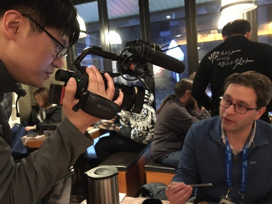 Sports Illustrated columnist Michael Rosenberg discusses his meal of grilled pork and kimchi fried rice with a man filming a commercial for a restaurant Tuesday in Gangneung, South Korea. Joe Rexrode/The Tennessean