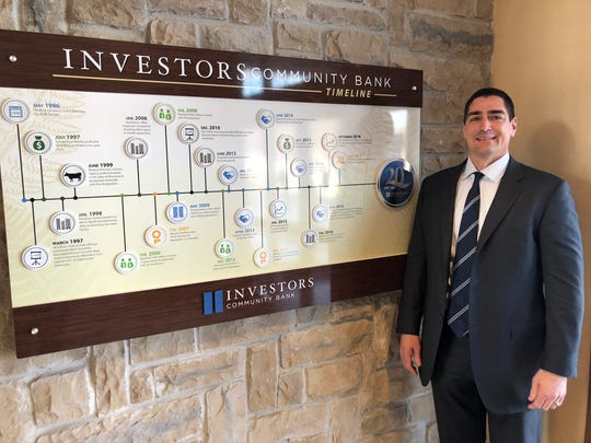 Tim Schneider, ICB CEO and co-founder, poses near the Investors Community Bank timeline display at the Manitowoc location. A timeline was installed at each location in honor of the bank's 20th anniversary in 2017.