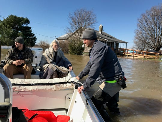 Nick Risley with the Zion Volunteer Fire Department maneuvers a boat carrying a hospice patient from his home which is cut off by flood waters