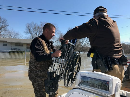Sheriff's Lt. Keith Berry and Sgt. Carroll Morrow unload a wheelchair from the boat after they helped evacuate an elderly man from his Hossman Newburgh residence. The home was cut off by flood waters.