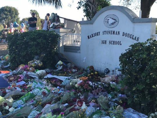 Flowers and messages are spread outside the chain link fence of Marjory Stoneman Douglas High School in Parkland.