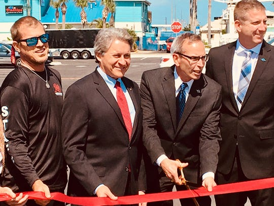 Officials prepare to cut the ribbon marking the opening of a new 337-space parking area at Port Canaveral's Cove area. From left are Cove Merchants Association President Rhett Fischer, Port Canaveral Chief Executive Officer John Murray, Canaveral Port Authority Chairman Wayne Justice  and Canaveral Port Authority Vice Chairman Micah Loyd.
