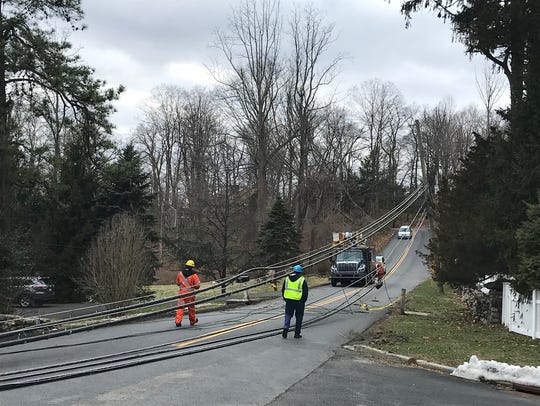 Utility crews on Monday night survey the downed power