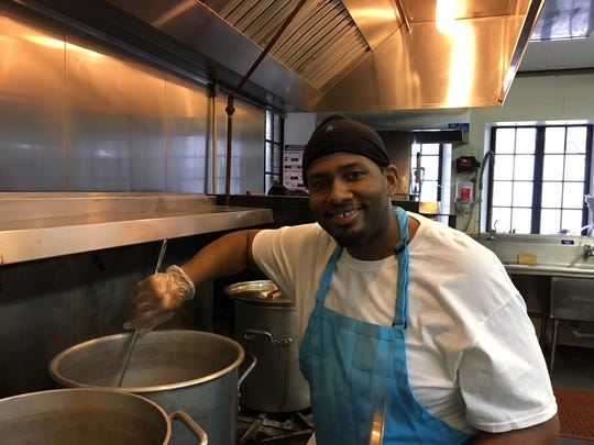 Dennis Woodfork stirs soup for guests of the Community