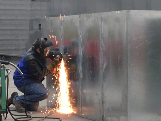 An employee at Robinson Metal, Inc. works on part of