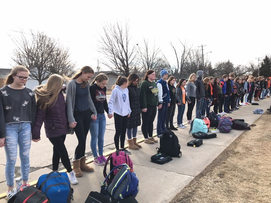 Students from Oshkosh West High School hold hands and face the school during a walkout to protest gun violence Wednesday.