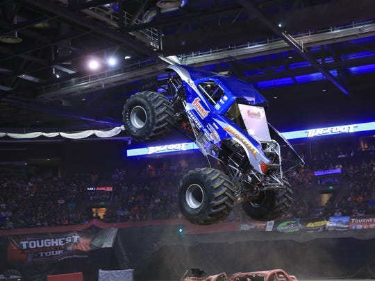 Bigfoot leaps over two cars during competition at the Toughest Monster Truck Tour.