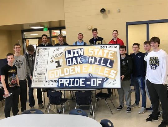 Oak Hill basketball players pose in front of a sign