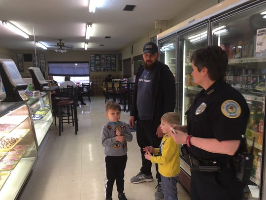 HPD Officer Jennifer Richmond gives stickers to Waylon Givens, 5, and Chance Givens, 4, as the boys get ready to choose their Golden Glaze goodies at a meet-the-police event.