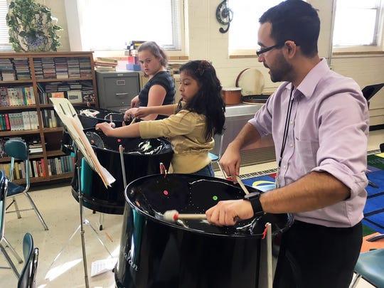 Betty Racanelli and Alia Hernandez work through a tricky steel drum part with their teacher, José Ramos Santiago.