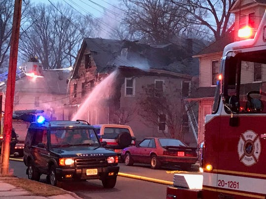 Firefighters pour water on a two-family home on Arlington Avenue in Plainfield.
