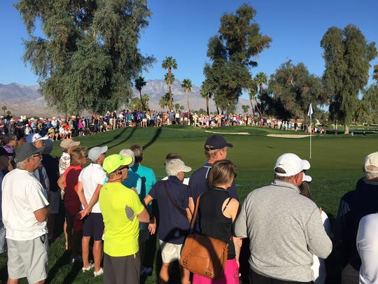 A large crowd rings the 10th green Monday morning during