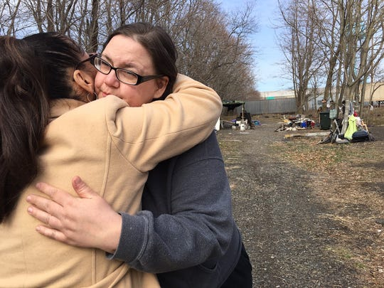 Sharyn Deloach (left) gives a hug to Melissa Gorski, wife of Robert Gorski, at the tent city where her husband lived.