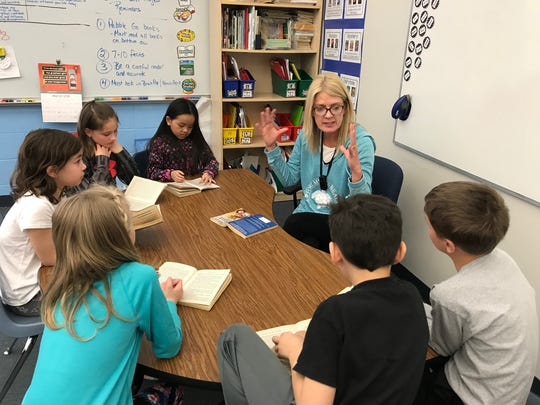 Suamico Elementary third-grade teacher and Golden Apple winner April White works with her students while they read The Mouse and the Motorcycle by Beverly Cleary.
