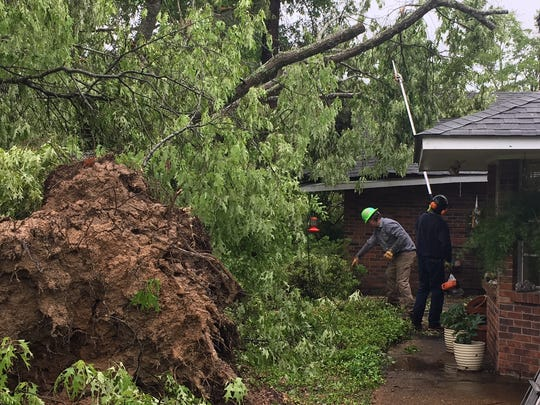 Workers cut limbs off a downed tree in the backyard of a residence in the Millcreek community in Rankin County after a tornado came through the area early Saturday morning. Much of the state was pelted by severe storms.