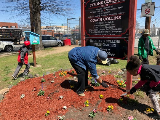 Jeanette Bugg, ( c ) and Emyla Greene ( r ), plant flowers in the Nazerah Bugg garden at Tyrone Collins park in Paterson.