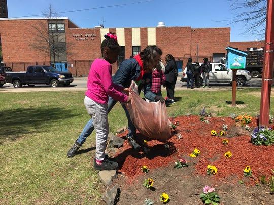 Faith Wells ( L ), and Marcella Simadiris adding mulch to the Nazerah Bugg garden.