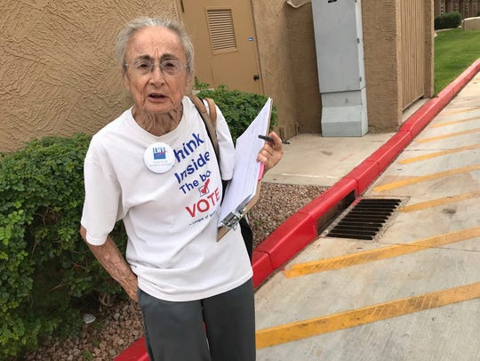In this April 19, 2018, file photo, Rivko Knox, of Phoenix, a volunteer with the League of Women Voters, collects signatures for a ballot measure on campaign financing outside a polling station in Glendale, Ariz. A lawsuit filed Tuesday, July 3, 2018, on Knox's behalf, seeks to overturn a 2016 law that bars groups in Arizona from collecting early mail-in ballots from voters and delivering them as part of get-out-the-vote efforts.