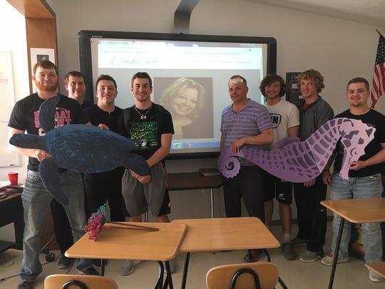 English teacher John David Thompson poses with students