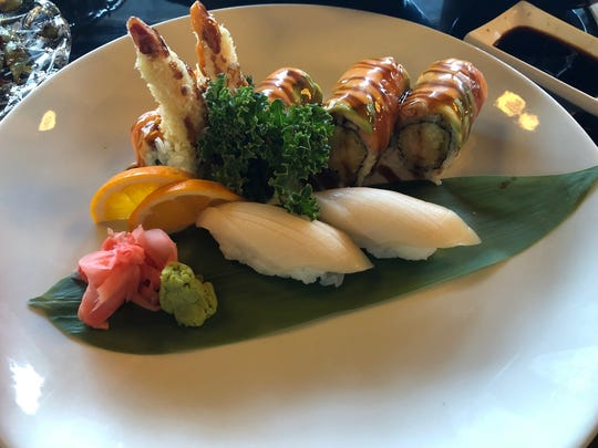 The Crazy Grills Roll at Katana has shrimp tempura, cucumber inside, topped with avocado , salmon, served with spicy mayo and eel sauce.