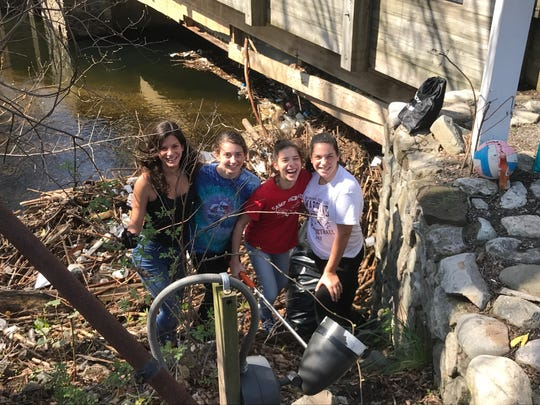 Park Ridge High School students cleaning a section of the Pascack Brook on Saturday are, L to R, Emma Ferranti, Alexa Cawood, Lauren Ferranti, and Erica Ferranti.