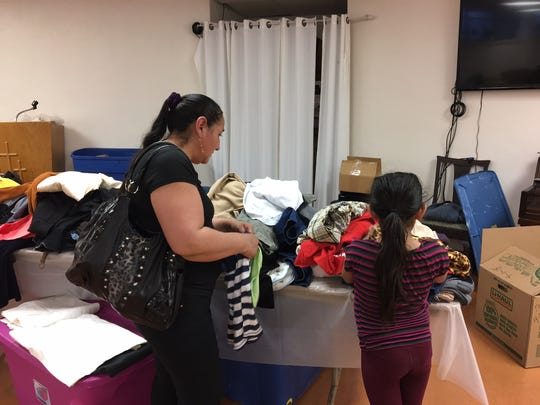 A mother and her daughter browse through donated clothing