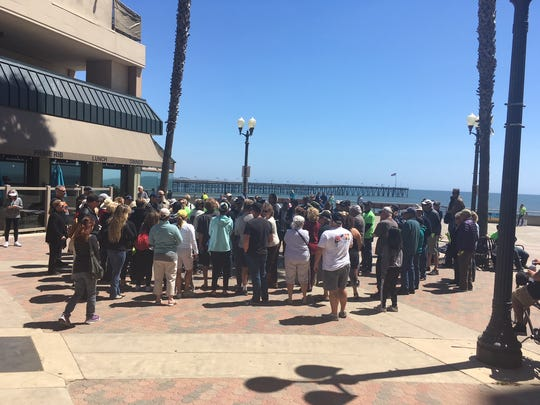 """A group gathers to watch and participate in the """"John and Ken"""" radio show at the Ventura Promenade on Thursday."""