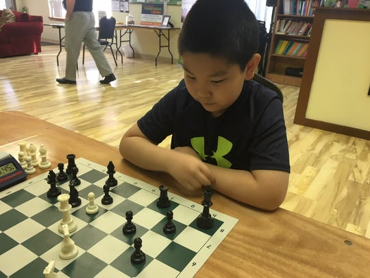 Maxwell Wang of Cherry Hill is shown studying the chessboard