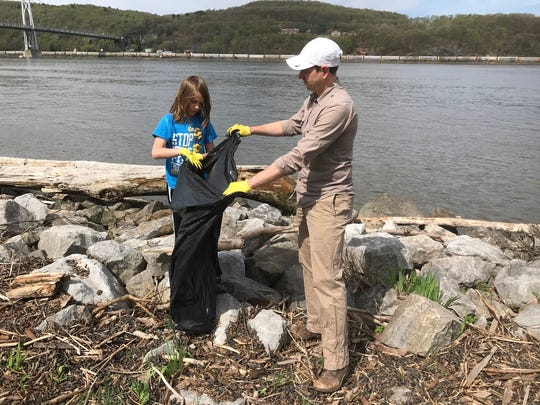 David Holdreith, a New York City resident who owns a weekend home in LaGrangeville, right, collects trash with his son, Henry, at Waryas Park in the city of Poughkeepsie in 2018. Holdreith and his family took part in the seventh annual Riverkeeper Sweep.
