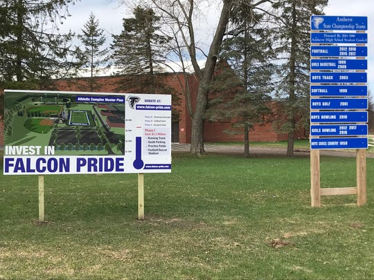 A sign with recent state champions at Amherst High School (right) stands next to a sign showing the progress on a fundraising campaign to expand the parking situation and upgrade the outdoor athletic facilities at the school.