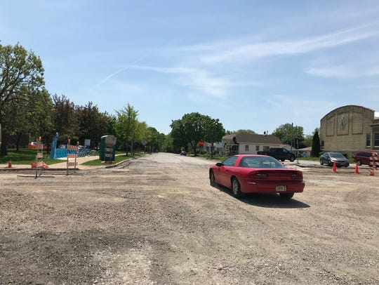 A car makes its way on 75th Street across a ripped-up and gravelly National Avenue toward the paved part of 75th and the West Allis Public Library parking lot.