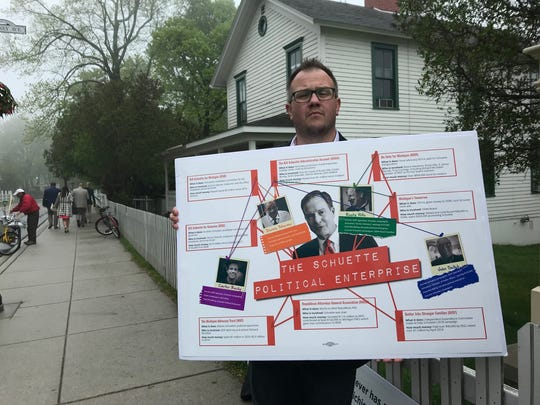 Progress Michigan Executive Director Lonnie Scott holds a poster board highlighting allegations against Attorney General Bill Shuette, outside the Mackinac Policy Conference on Mackinac Island Thursday.
