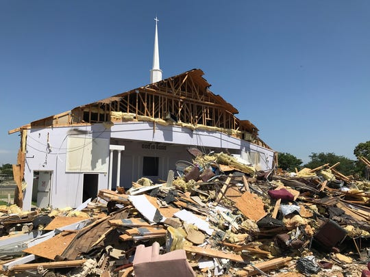 "A sign behind the pulpit at Victory Christian Center, 1620 Sunset Drive, proclaiming ""GOD IS GOOD"" is visible from the parking lot after the church's roof collapsed on May 25. Members of the congregation joined local contractors in pulling down walls to prevent further collapses."