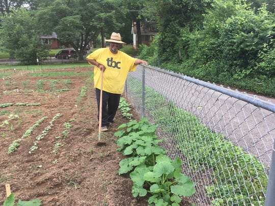 "The Rev. Chris Battle beside the ""Gleaning Fence."""