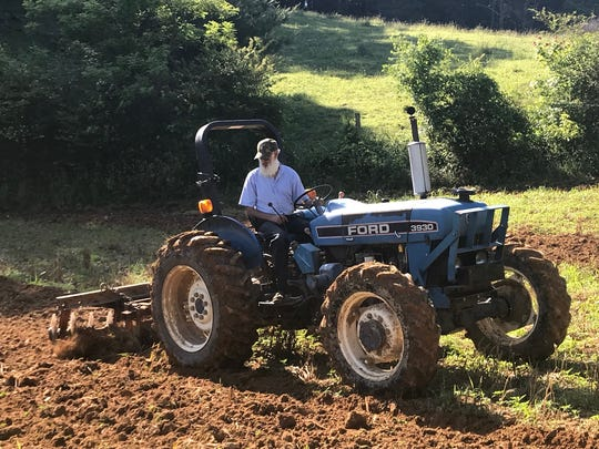 Buster Norton, here prepping a tobacco field along NC 213 in 2018, drove over Walnut Mountain four times a day as a school bus driver before a landslide on Walnut Creek Road changed his route.