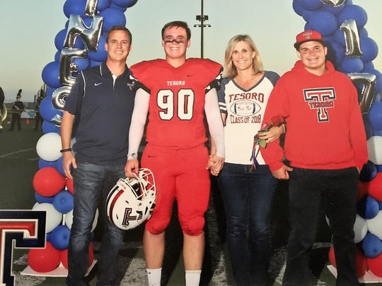 Kurt, left, celebrates senior night for his son, Corbin (90), at Tesoro High School in Rancho Santa Margarita, Calif. He's joined by his wife, Amy, and their youngest son, Johnny.