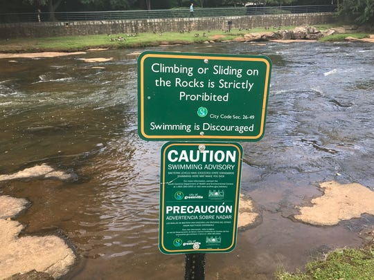 A sign along the Reedy River at Falls Park warns visitors not to go swimming here. (Do you see the typo?)