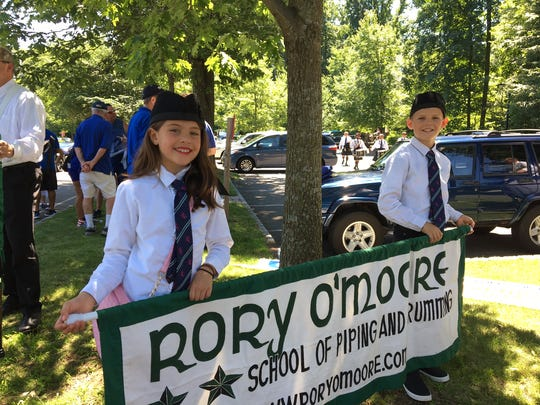 Madison and Michael Johnson prepare to march with Rory O'Moore Pipes and Drums at the Randolph Kiwanis Freedom Parade, June 30, 2018