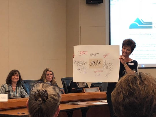 In this file photo, Larimer County Behavioral Health Director Laurie Stolen holds up a sign a speaker brought to a commissioners meeting, during which commissioners unanimously referred a question to the November ballot on funding a mental and behavioral health facility. The measure was approved.