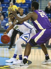 Delaware guard Ryan Allen (left) slips a pass past James Madison's Dwight Wilson at the Bob Carpenter Center.