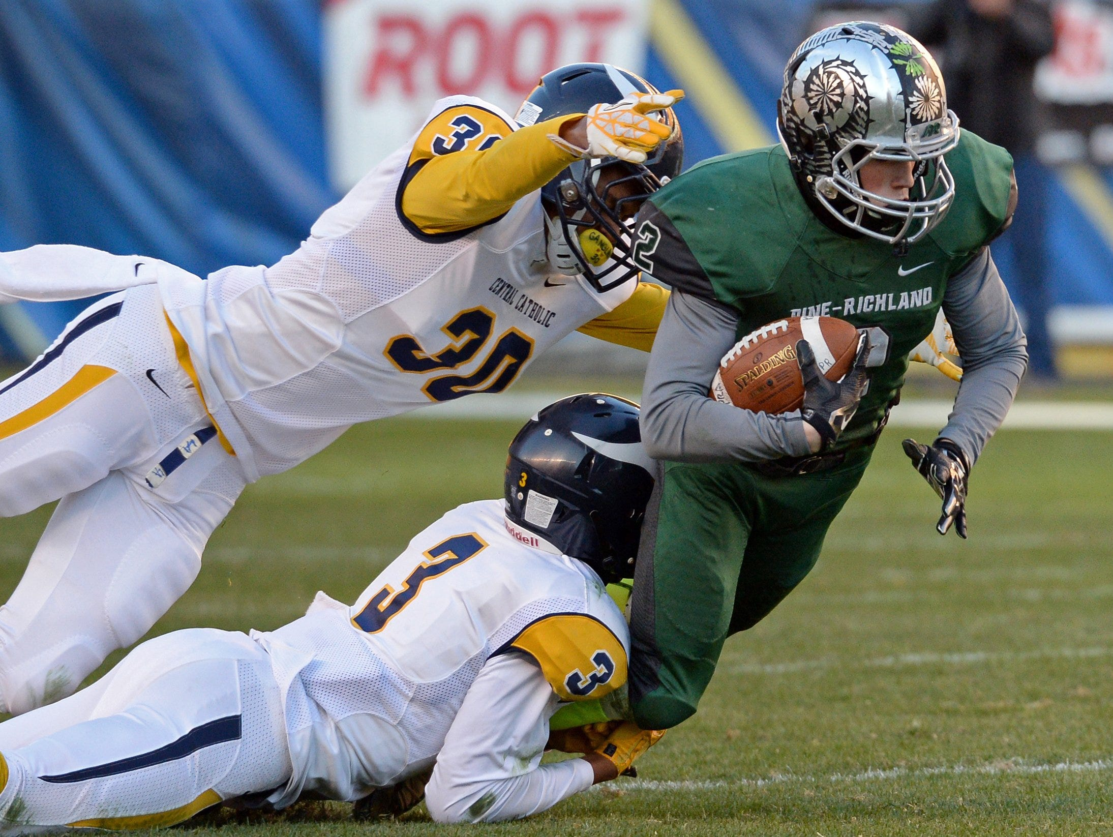 Pine-Richland's Michael Merhaut, right, carries the ball as he's taken down by Pittsburgh Central Catholic's Damar Hamlin (3) and Bryan Glover (30) on Nov. 21, 2014, in Pittsburgh.