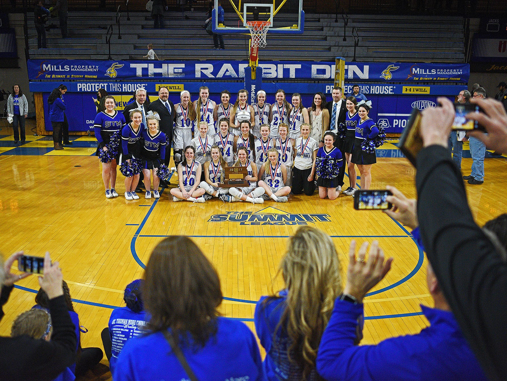 St. Thomas More player pose for photos after their 47-36 win over Lennox in the 2017 SDHSAA Class A State Girls Basketball Tournament championship game for their fourth consecutive title Saturday, March 11, 2017, at Frost Arena on the South Dakota State University campus in Brookings, S.D.