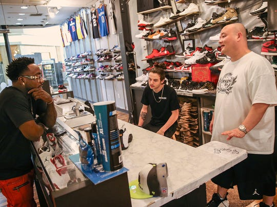 From right, owner Paul Zigrang and employee Hadyn Mayes help a customer at Grails Inc., in Washington Square Mall, Indianapolis, Wednesday, May 31, 2017. The shoe store specializes in hot-selling, collectible new and used sneakers. Zigrang's brick and mortar shop opened a little over a year ago and has done so well, a second location opened in the Greenwood Park Mall.