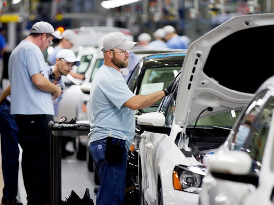 Workers attend to Volkswagen Passat sedans on the line
