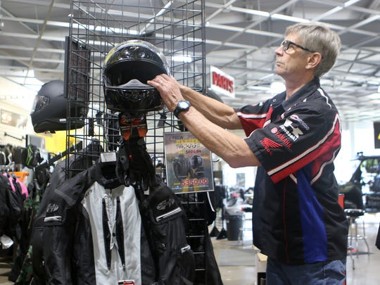 Stewart Crouch, owner of Diamond Motorsports in Camden, checks out a display featuring a motorcycle helmet and other safety equipment he urges all new buyers to purchase before getting out on the road.