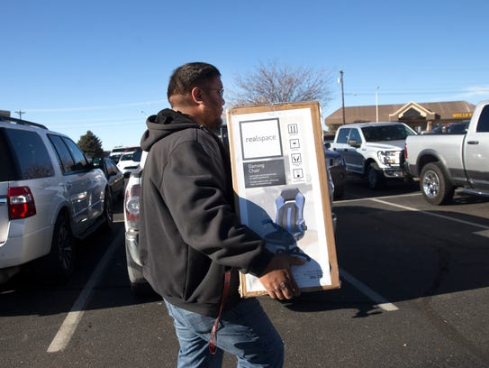 Shopper Loren Harrison carries his purchases to his vehicle Friday at the Four Corners Marketplace in Farmington